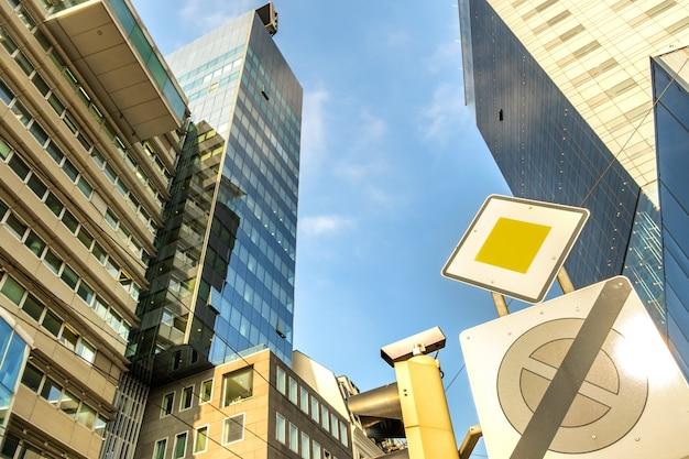 Vista em perspectiva do moderno arranha-céu de vidro e do sinal de trânsito da estrada principal.
