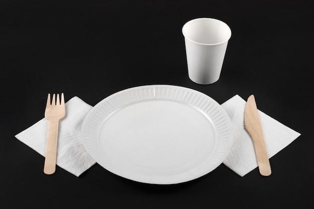 Vista em perspectiva do prato de papel branco, copo de papel, garfo de madeira e faca no guardanapo branco sobre fundo preto, vista superior. conjunto de talheres descartáveis ecológicos de material natural.