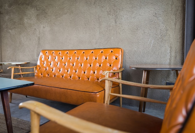 Vista em perspectiva e sofá de madeira vintage luz quente na bela sala interior fundo de concreto