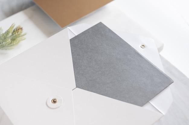 Vista em perspectiva superior do cartão cinzento em branco em envelope branco com folha de pinheiro na mesa de mármore