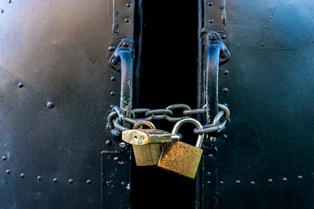 Vista em porta metálica trancada com três cadeados