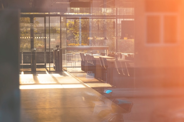Vista em um café vazio através do vidro com reflexão. primavera brilhante luz da manhã.