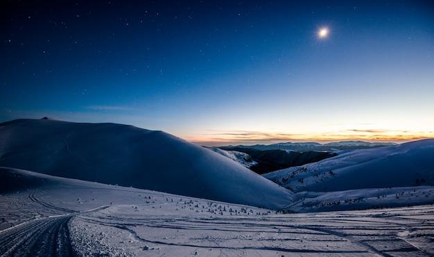 Vista encantadora de uma estação de esqui vazia sob o luar à noite