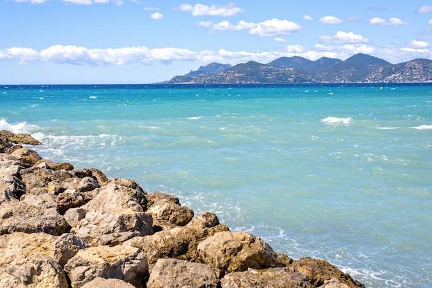 Vista ensolarada do dia das rochas ao mar e às montanhas azuis