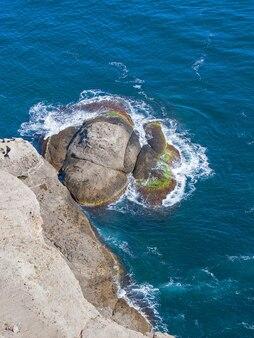 Vista ensolarada na água do mar azul em uma rocha alta