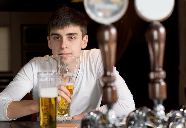 Vista entre as torneiras de cerveja em um distribuidor de um jovem sério bebendo sozinho