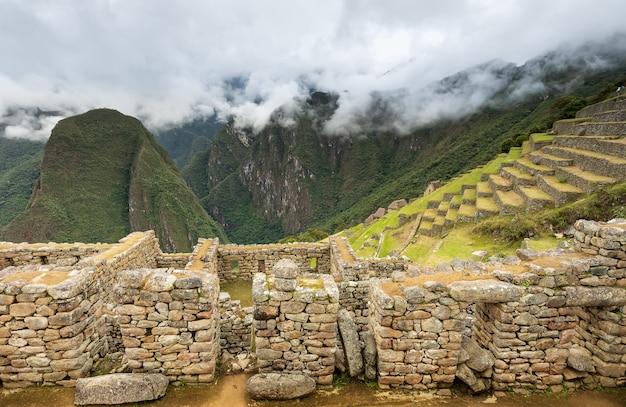 Vista estreita das ruínas na cidadela de machu picchu, terraço e montanhas nas nuvens, peru