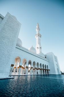 Vista exterior da enorme mesquita branca com alta torre branca