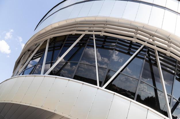 Vista externa das janelas de vidro preto hemisférico do edifício branco refletindo a rua