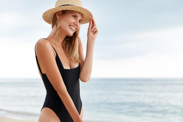 Vista externa de uma jovem modelo feminina de biquíni e chapéu de palha, de aparência agradável, com uma expressão sonhadora, desfruta de uma bela vista do mar e do nascer do sol, passa as férias de verão na praia nos trópicos