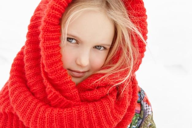 Vista externa de uma linda criança europeia com cabelo loiro posando do lado de fora durante uma curta caminhada