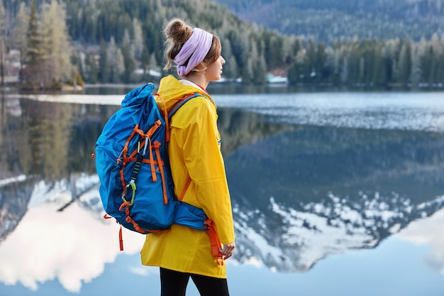 Vista externa de uma mulher relaxada e pensativa perto de um lago calmo com reflexo da montanha