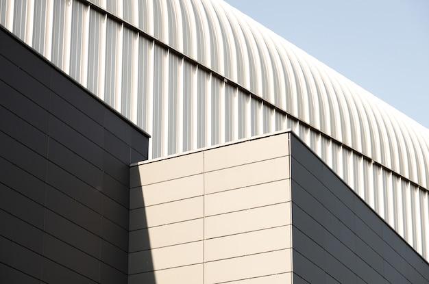 Vista externa do prédio com paredes de metal e telhado arqueado de cor cinza claro
