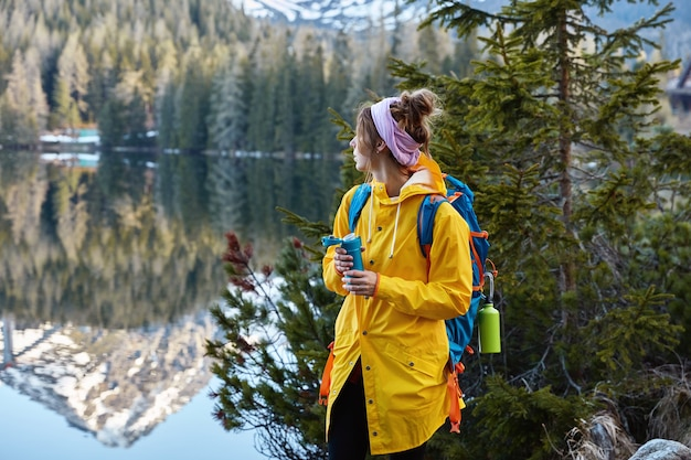 Vista externa horizontal de uma turista calma admirando belas montanhas, floresta e lago, mantendo o olhar de lado