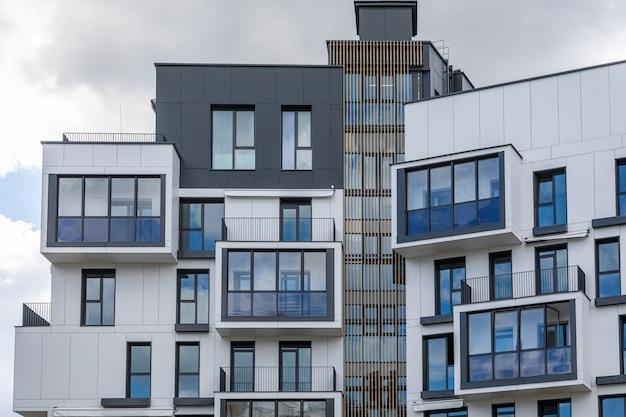 Vista externa nos andares superiores do moderno edifício branco e cinza com varandas