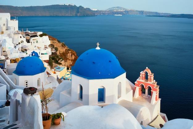 Vista famosa da vila de santorini oia com a cúpula azul da igreja cristã ortodoxa grega
