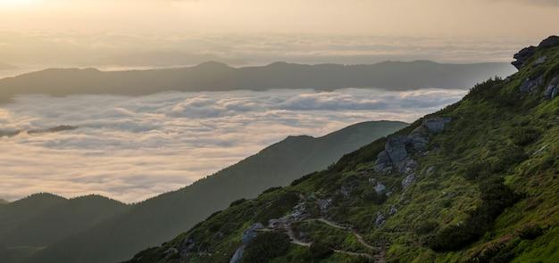 Vista fantástica do vale da montanha coberta com baixo branco inchado como nuvens de neve, estendendo-se para o horizonte nebuloso sob o céu brilhante da manhã com brilho laranja claro ao nascer do sol. beleza do conceito de natureza.