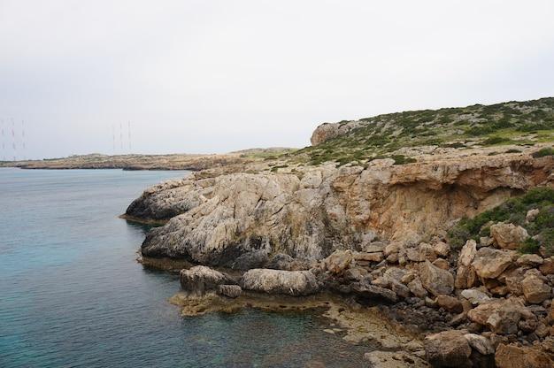 Vista fascinante da costa de um oceano com montanhas rochosas sob o céu azul