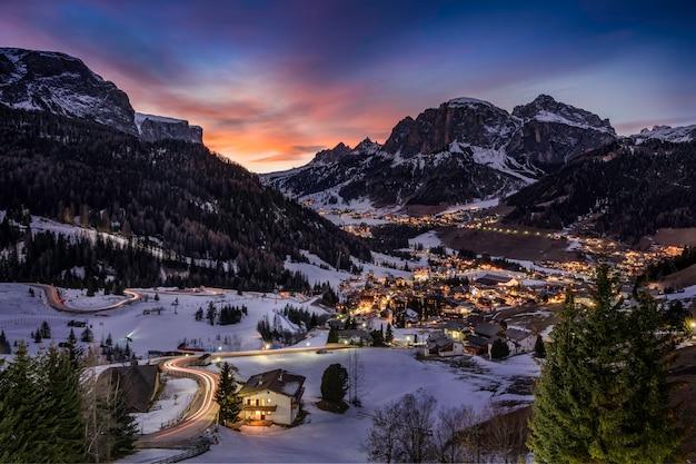 Vista fascinante das casas nos campos cobertos de neve cercados por montanhas e árvores