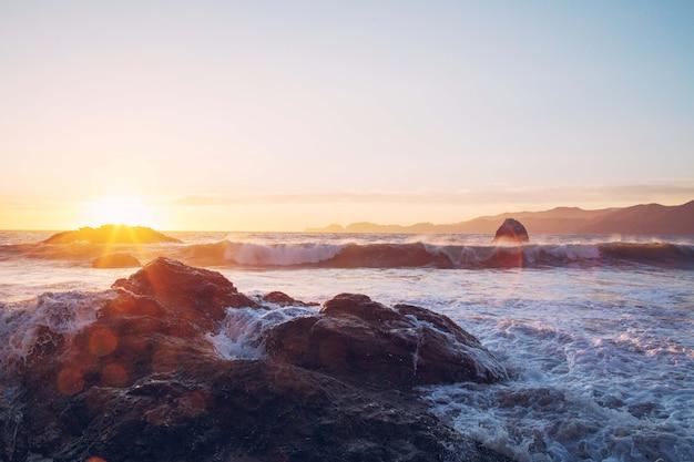 Vista fascinante das ondas do mar batendo nas rochas perto da costa durante o pôr do sol