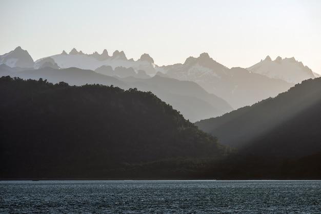 Vista fascinante das silhuetas das montanhas atrás do oceano calmo durante o pôr do sol