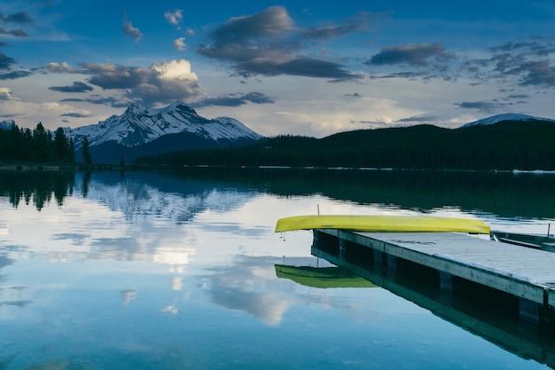 Vista fascinante do cais perto do lago rodeado pela natureza exuberante e as montanhas