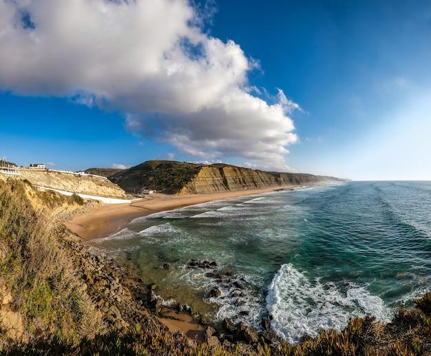 Vista fascinante do litoral cercado por montanhas rochosas sob o céu azul