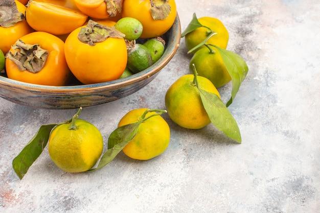 Vista fresca de feijoas de caqui em uma tigela e tangerinas em espaço livre com fundo nu