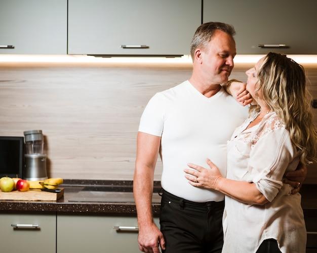 Vista frontal afetuoso casal sênior dentro de casa
