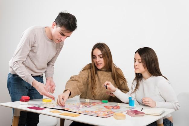 Vista frontal amigos jogando um jogo de tabuleiro