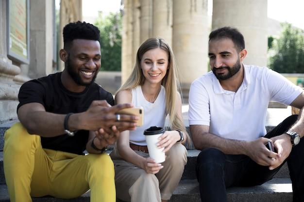 Vista frontal amigos multiétnicas sentado
