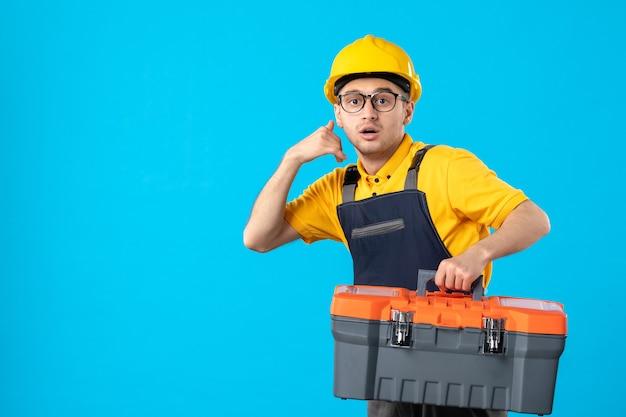 Vista frontal apressada trabalhador masculino em uniforme amarelo com caixa de ferramentas azul