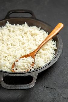 Vista frontal arroz cozido dentro da panela no escuro mesa refeição comida arroz jantar oriental