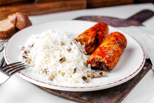 Vista frontal, arroz cozido, juntamente com carne e feijão dentro de chapa branca na mesa de madeira marrom e superfície