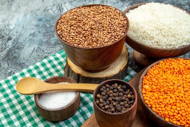 Vista frontal arroz cru com lentilhas de laranja e trigo sarraceno no fundo escuro farinha de sementes de sêmolas cor de cereais alimentos