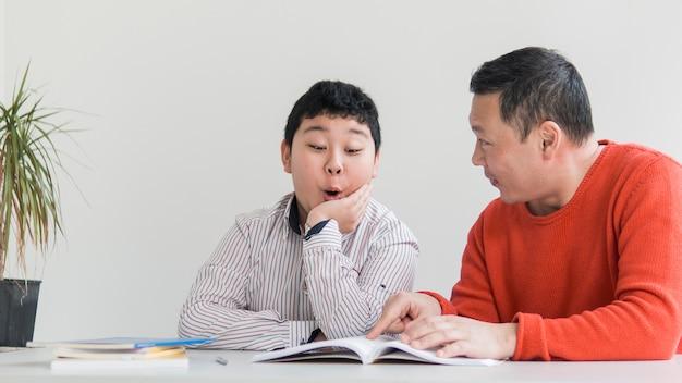 Vista frontal asiático pai e filho conversando