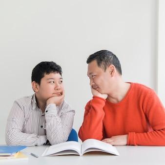Vista frontal asiático pai e filho dentro de casa