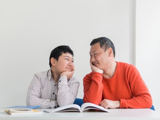 Vista frontal asiático pai e filho olhando uns aos outros