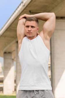Vista frontal atlético homem alongamento