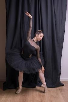 Vista frontal bailarina posando dentro de casa