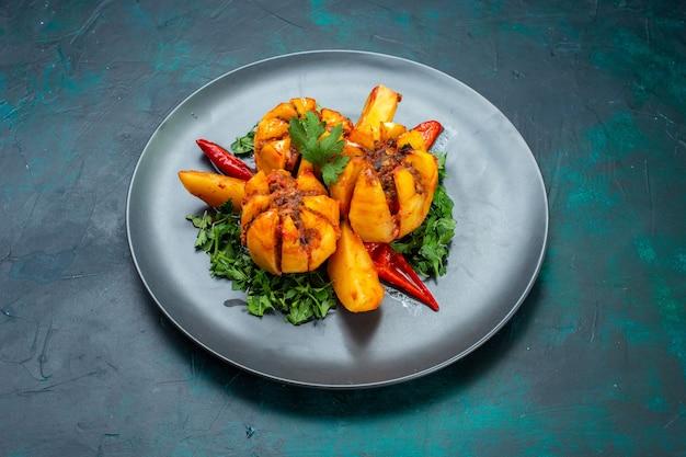Vista frontal batatas assadas com carne picada e verduras dentro da placa na mesa azul escura.