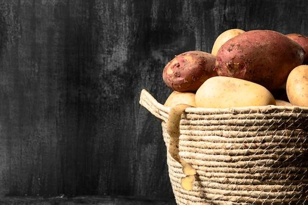 Vista frontal batatas na cesta com espaço de cópia