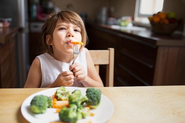 Vista frontal bebê menina com legumes