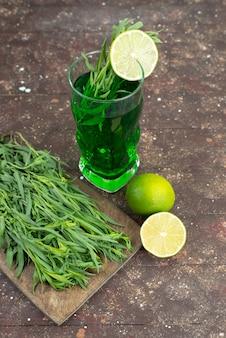 Vista frontal bebida de estragão fresco dentro de copo longo com folhas de estragão fresco em marrom, suco de bebida verde estragão