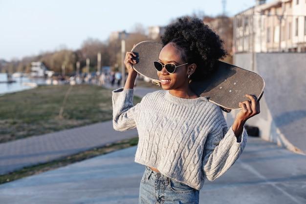Vista frontal bela jovem segurando um skate