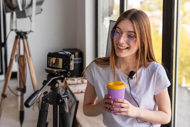 Vista frontal blogger gravação com câmera profissional, segurando uma caneca de viagem