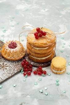 Vista frontal bolinhos com creme e biscoitos recheados na superfície clara doce chá açúcar