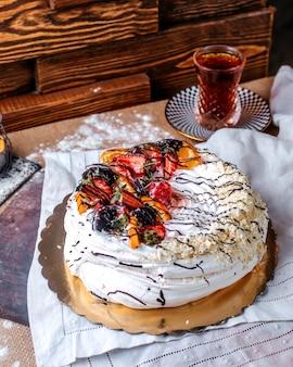Vista frontal bolo branco saboroso doce, juntamente com frutas fatiadas em cima e chá quente na mesa marrom