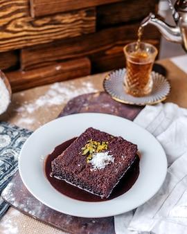 Vista frontal bolo de chocolate saboroso dentro de chapa branca, juntamente com chá quente na superfície marrom