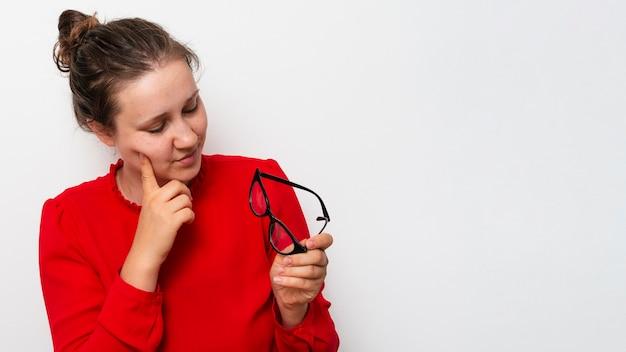 Vista frontal bonita mulher segurando óculos